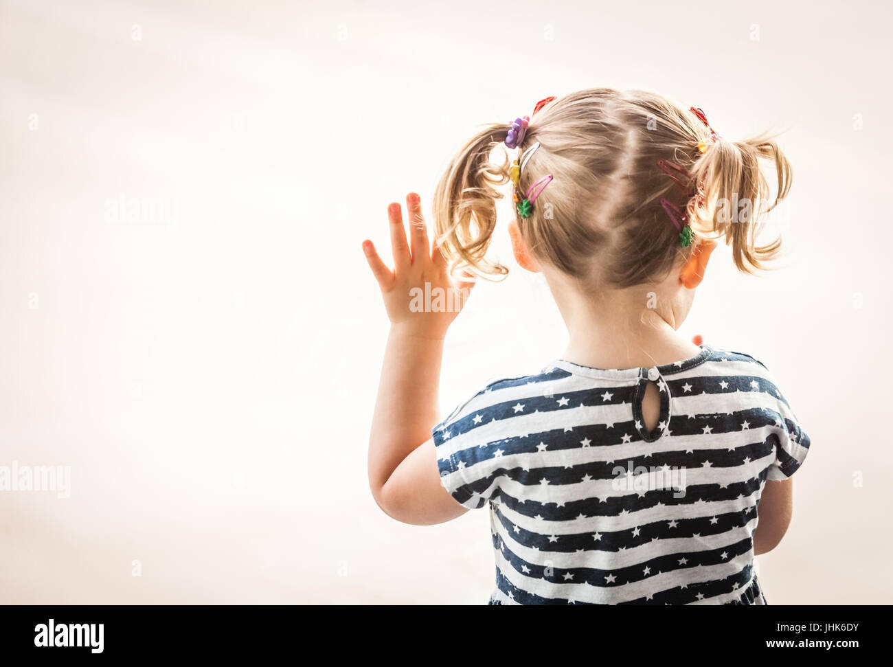 Little baby girl looking through the large window at the airport - Stock Image