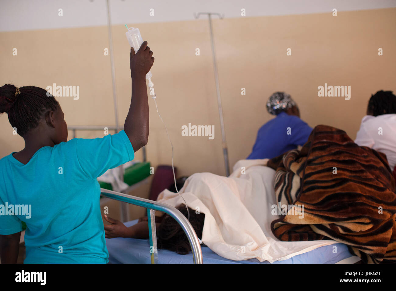 A relative holds up the drip while the nurse checks the patient at Kasangati Health Centre in Uganda. - Stock Image