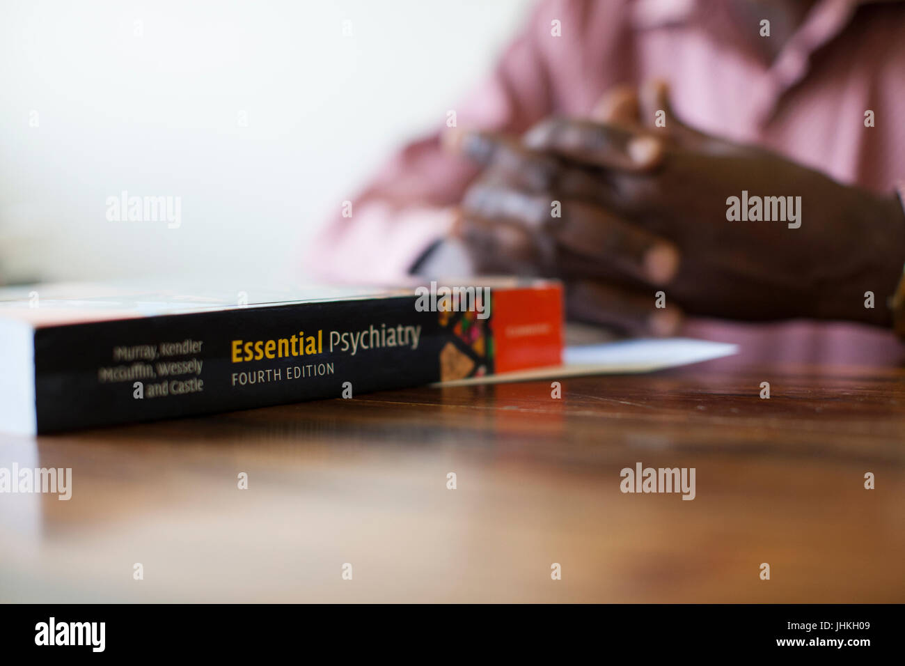 A book called Essential Psychiatry sitting in front of someone on a desk. - Stock Image
