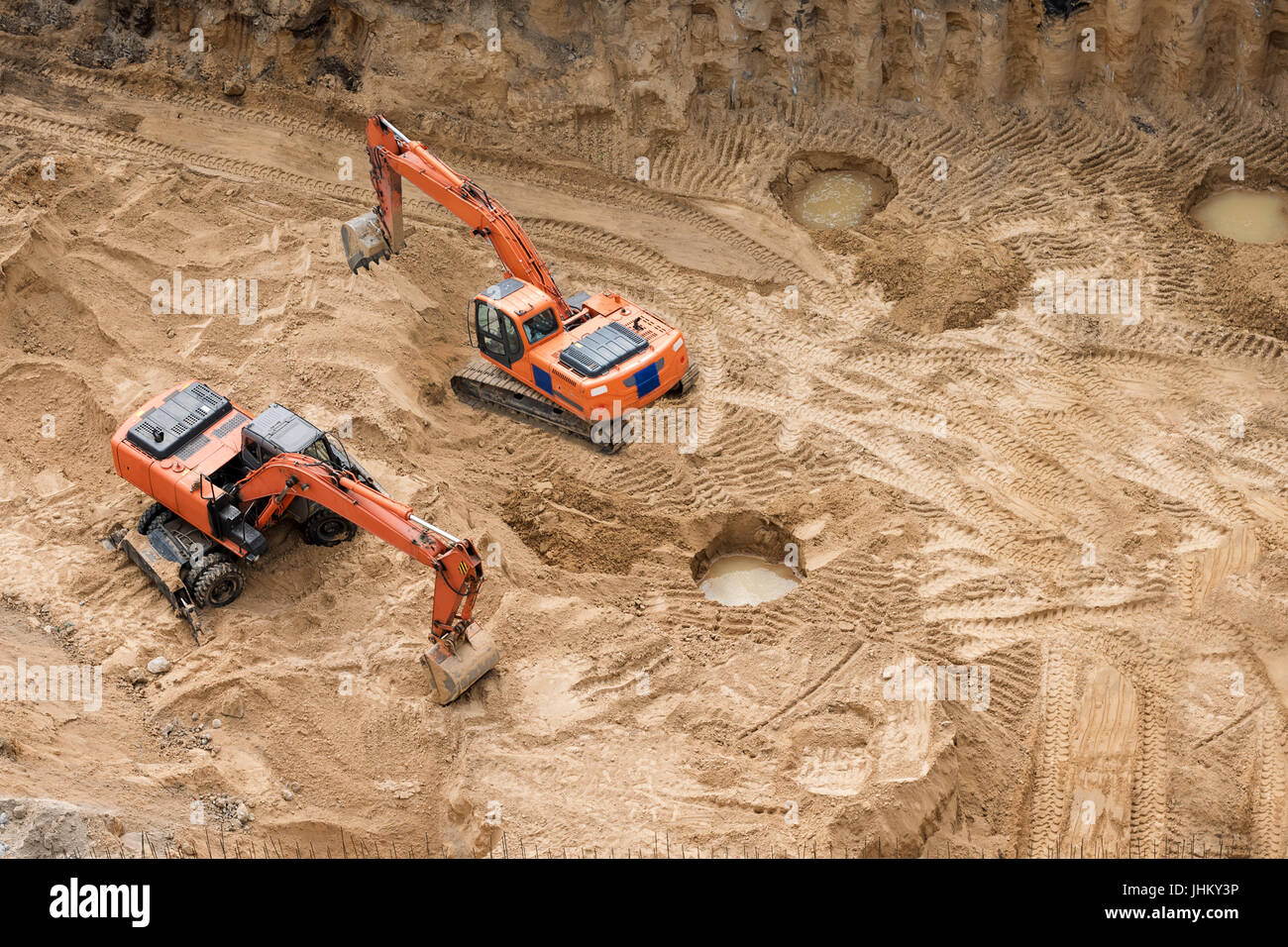 Excavators at sandpit during earthmoving works. Construction of concrete foundation of new building. - Stock Image