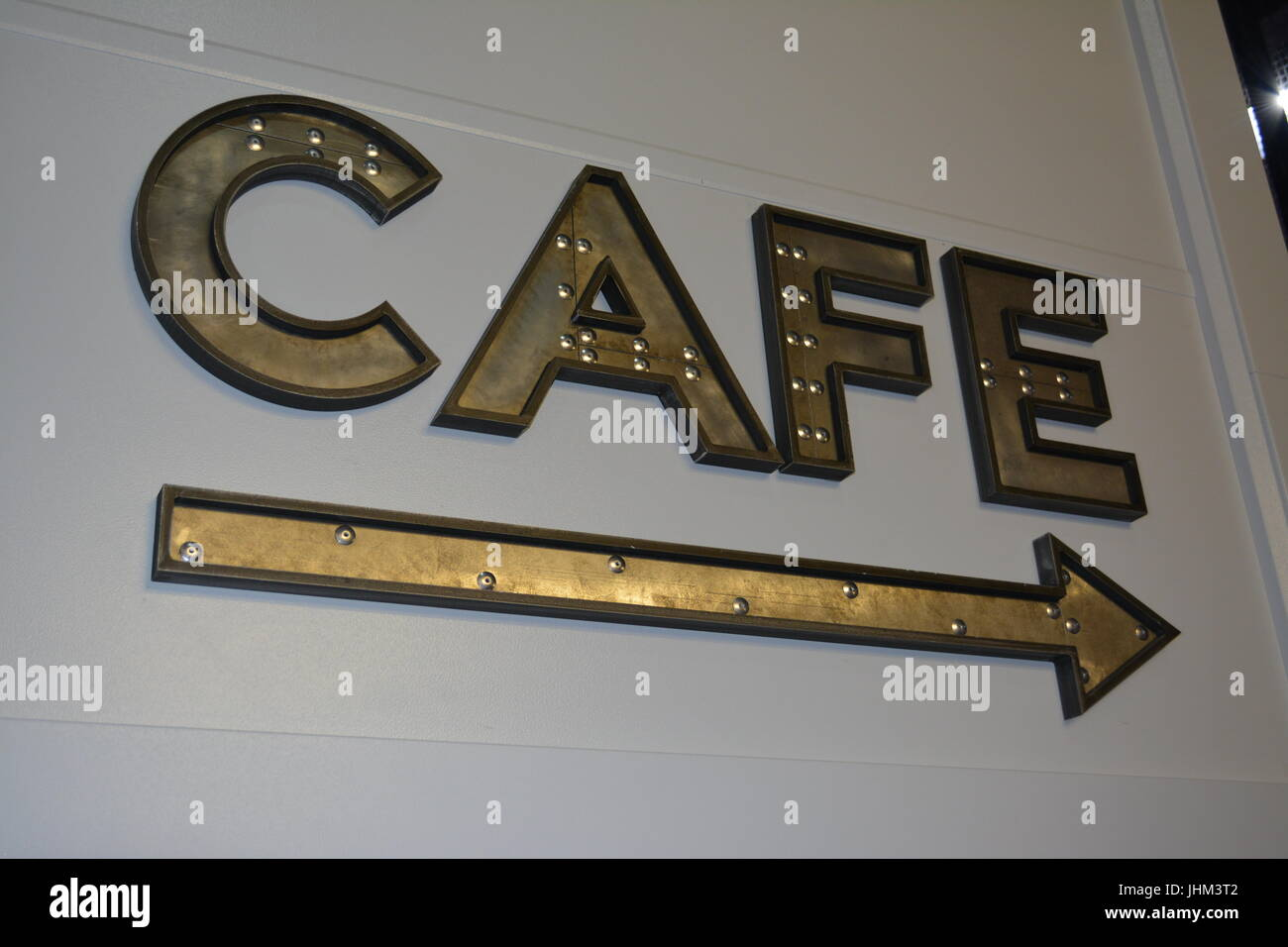 Large metal letters direction sign and arrow pointing to cafe re indoor cafe sign re eating and drinking re socialising - Stock Image