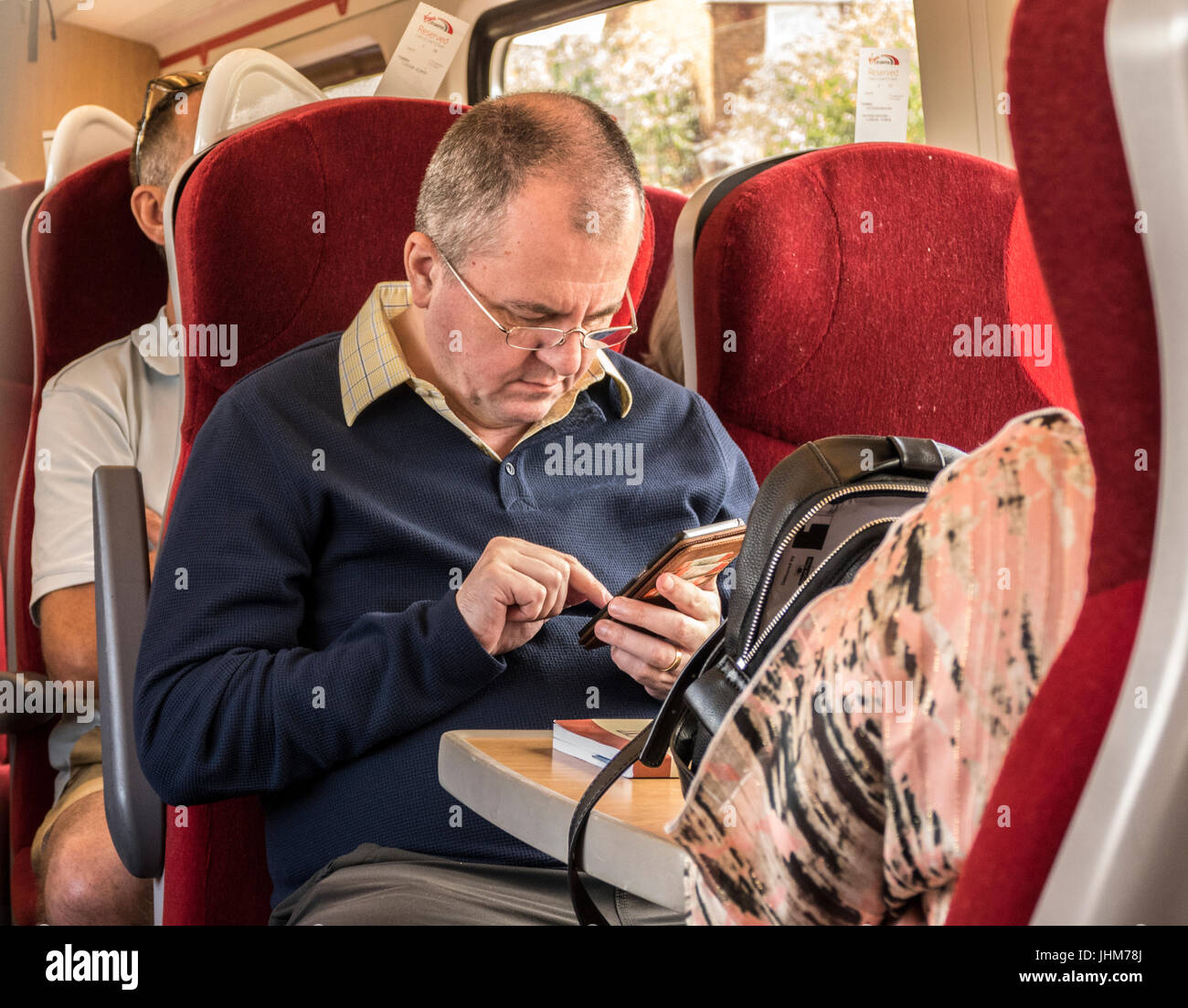 A middle aged man using his mobile phone on a train in England. UK. - Stock Image
