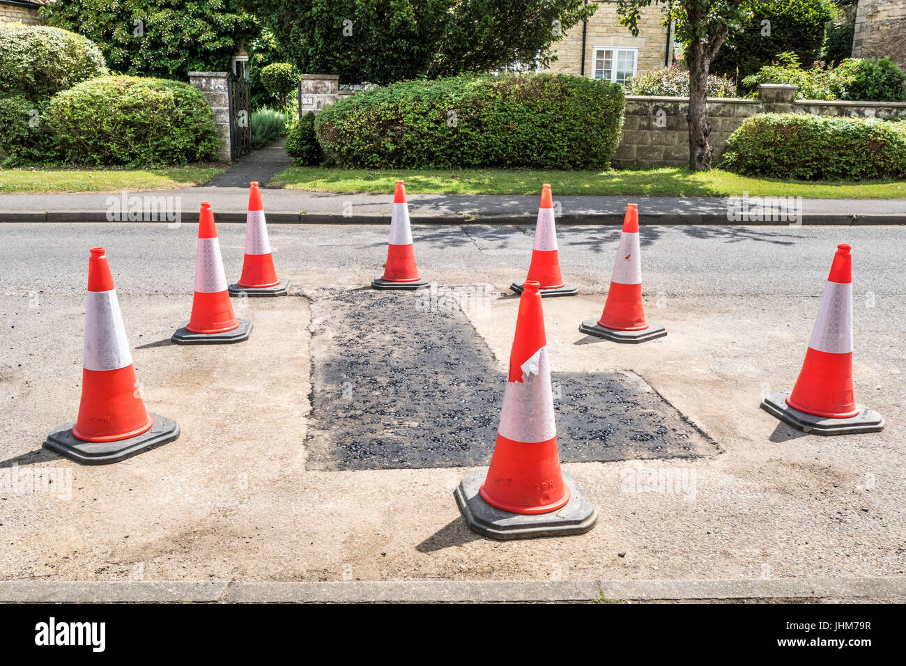 Cones around newly laid Tarmac in Langtoft village, Lincolnshire, England, UK. - Stock Image