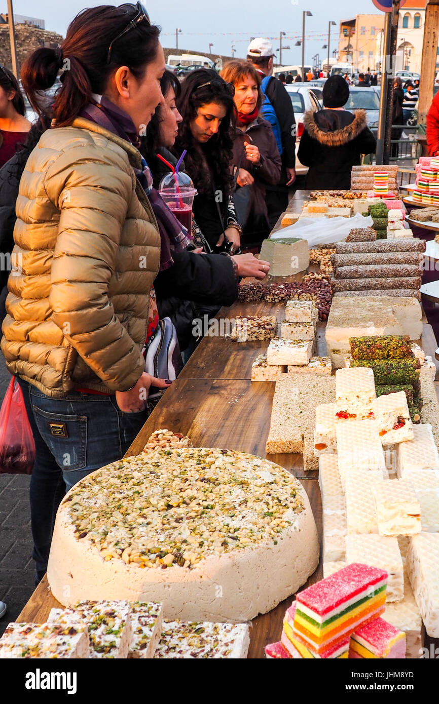 Women buying Israeli sweet halva at a stall in an outdoor market in Acre, Israel. - Stock Image