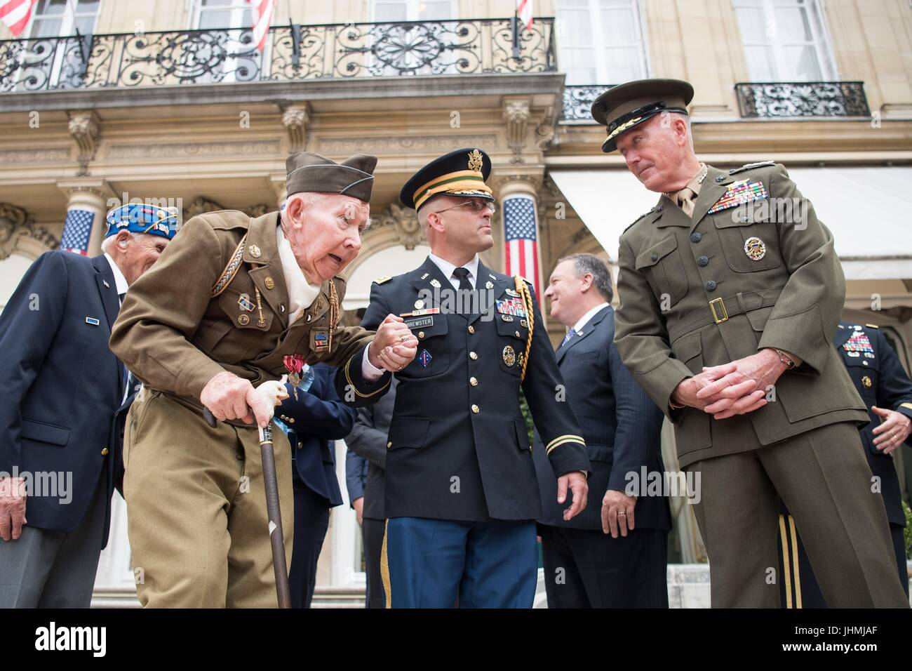 U.S. Army Lt. Col. Jessie Brewster, center, escorts World War II veteran Pvt. Joseph Reilly, left, to his seat as - Stock Image