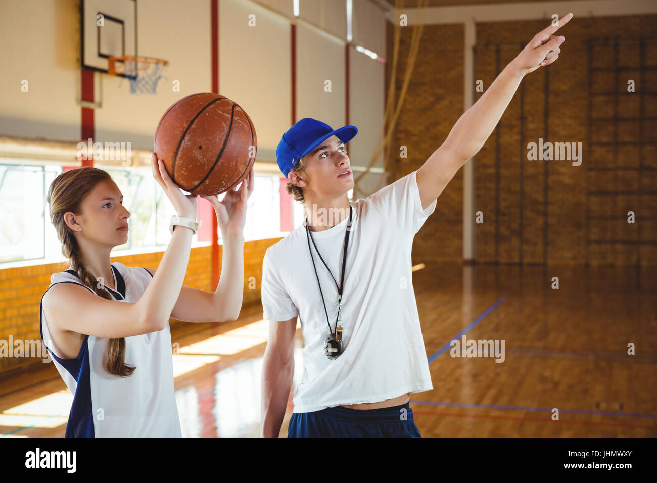 Male coach advising female basketball player while practicing in court - Stock Image