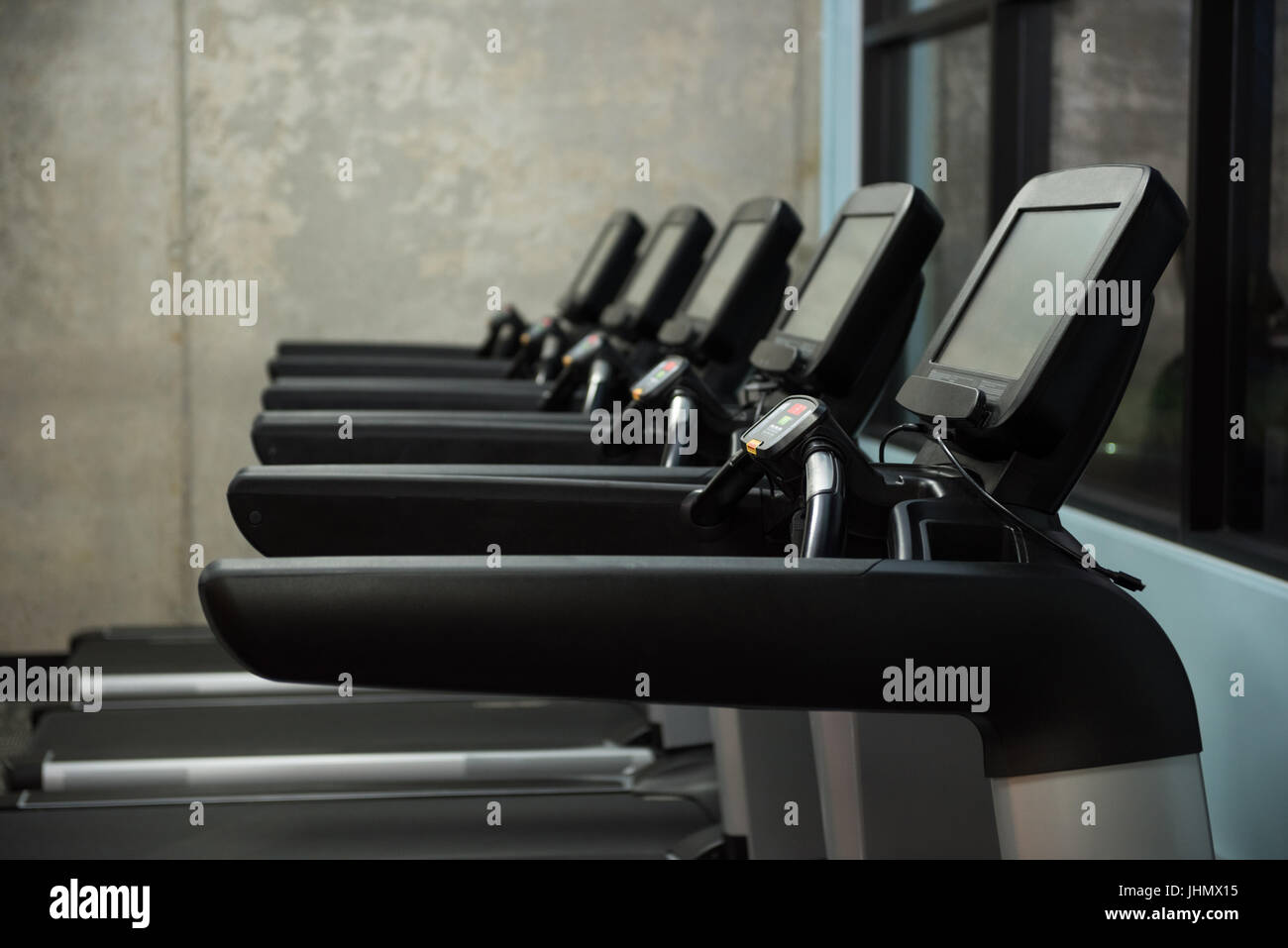 Treadmills in row against wall at empty gym - Stock Image