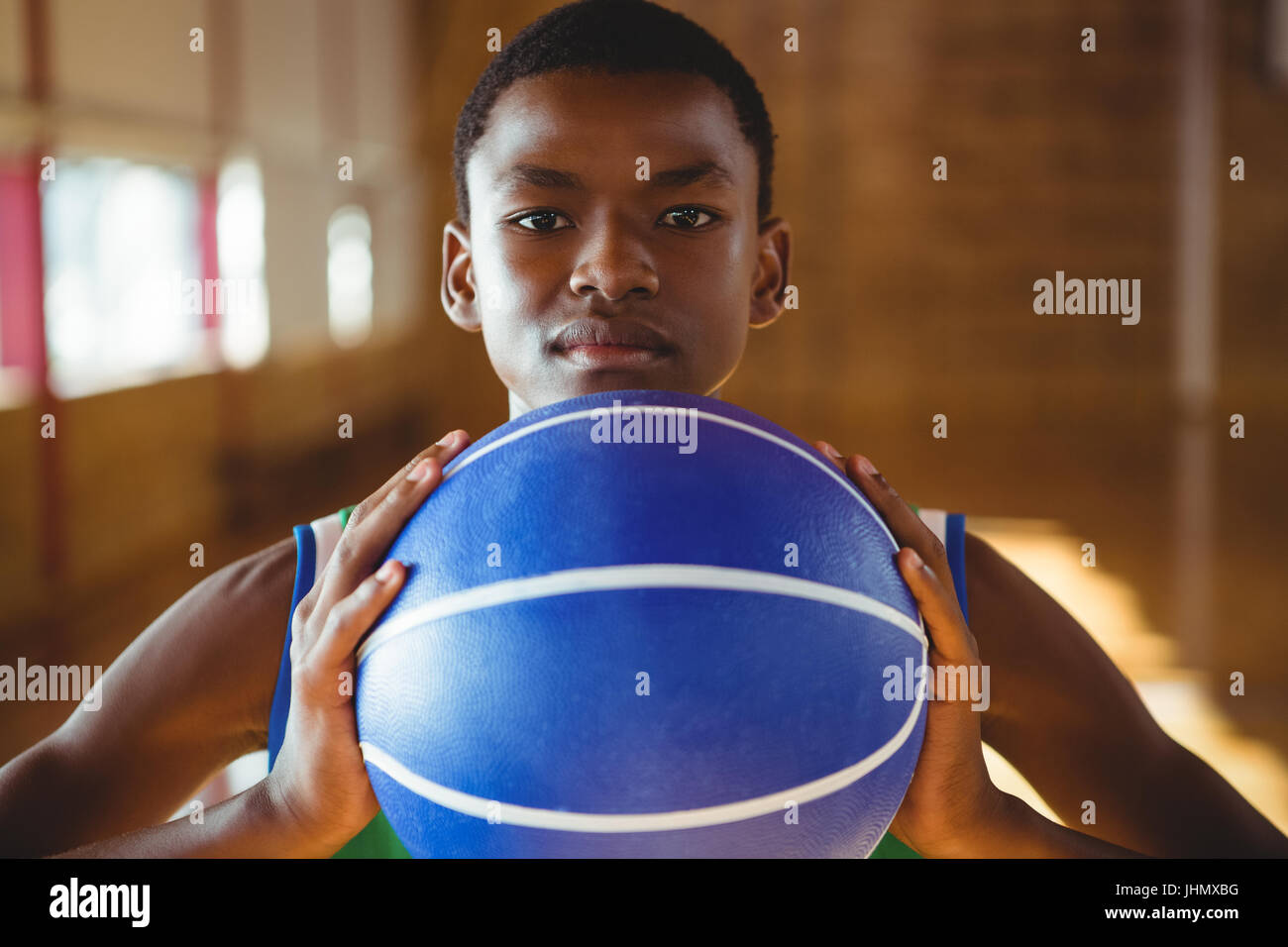 Close up portrait of serious man with basketball standing in court Stock Photo