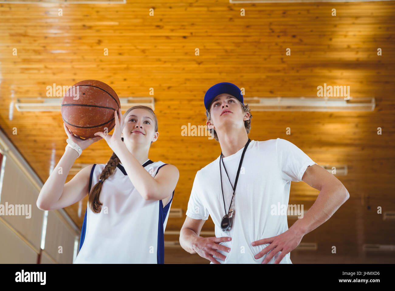 Low angle view of male coach advising female basketball player while practicing in court - Stock Image