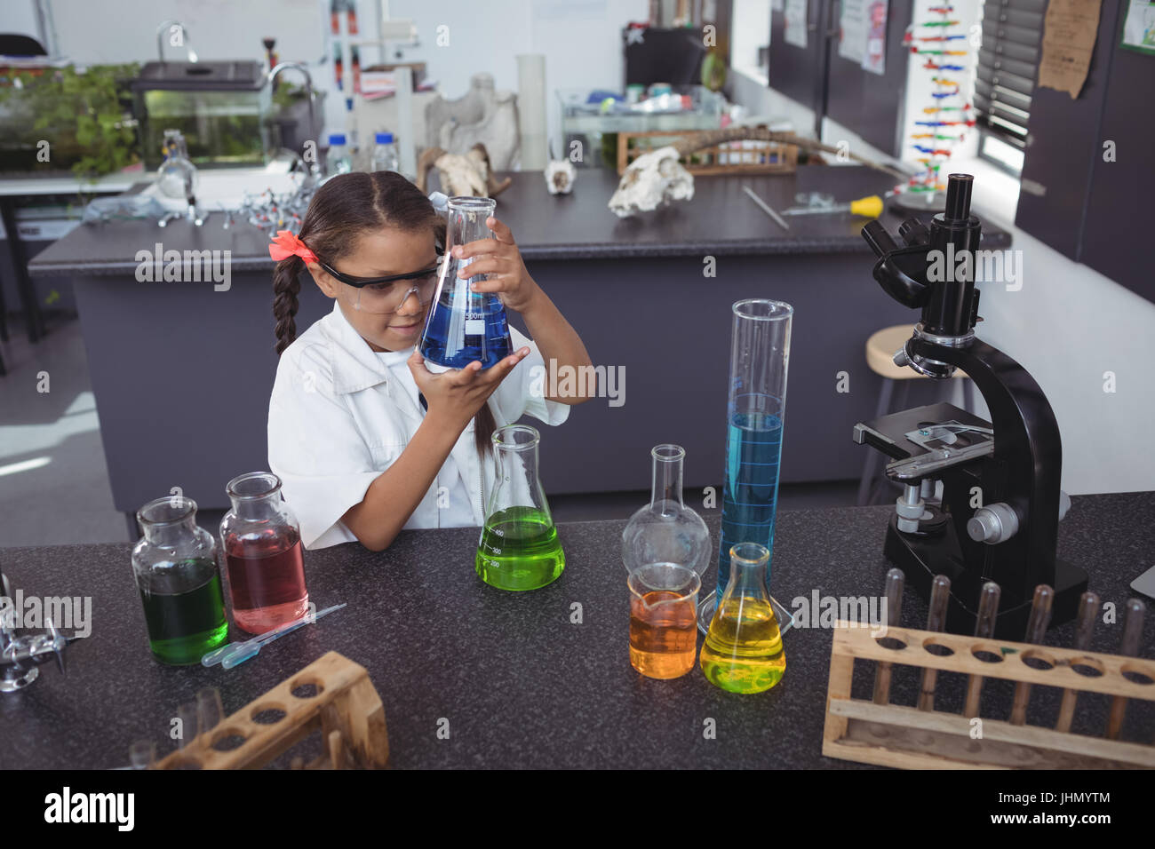 High angle view of elementary student examining blue chemical in flask by desk at science laboratory Stock Photo
