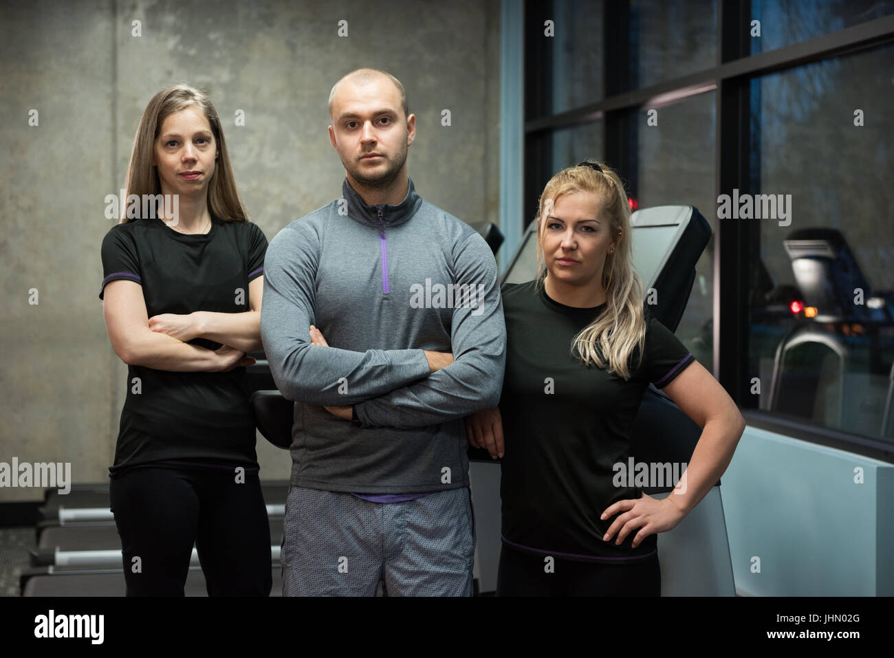 Portrait of young friends standing against treadmills at gym - Stock Image