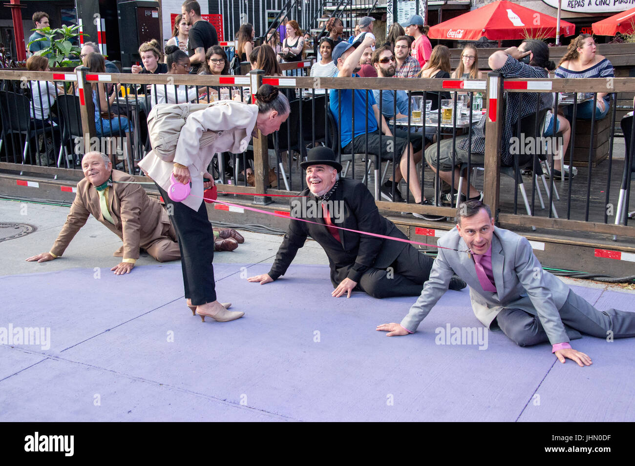 Montreal, Canada - 13 July 2017: Woman walking three men on dog leashes during Montreal Circus Festival - Stock Image