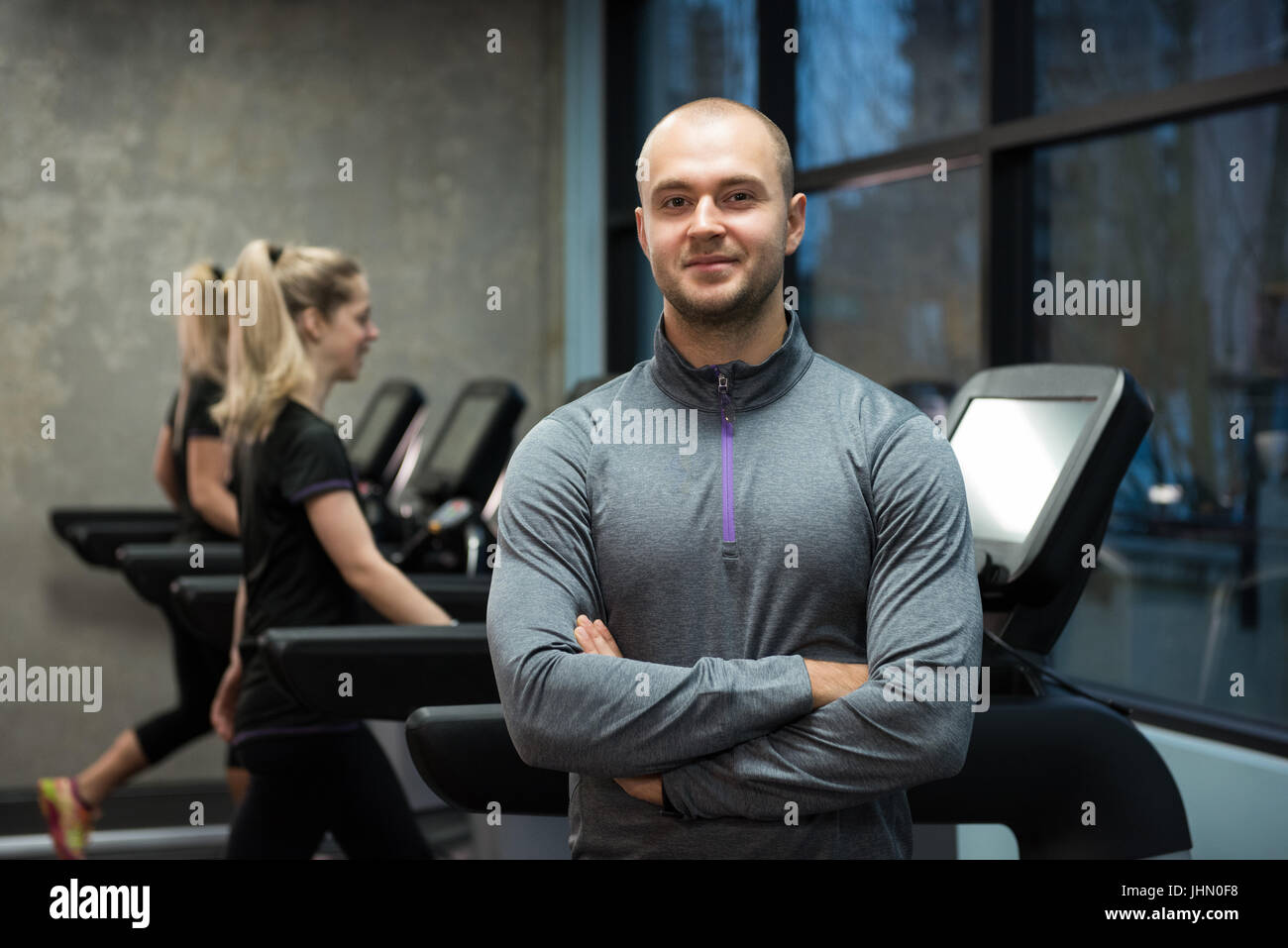 Portrait of man standing with women exercising on treadmills at gym - Stock Image