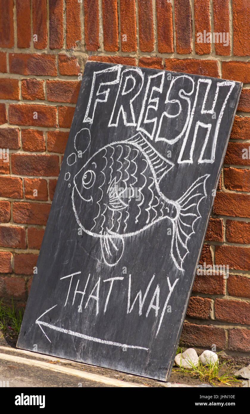 Fresh Fish that way sign on blackboard at Lyme Regis, Dorset in July - Stock Image