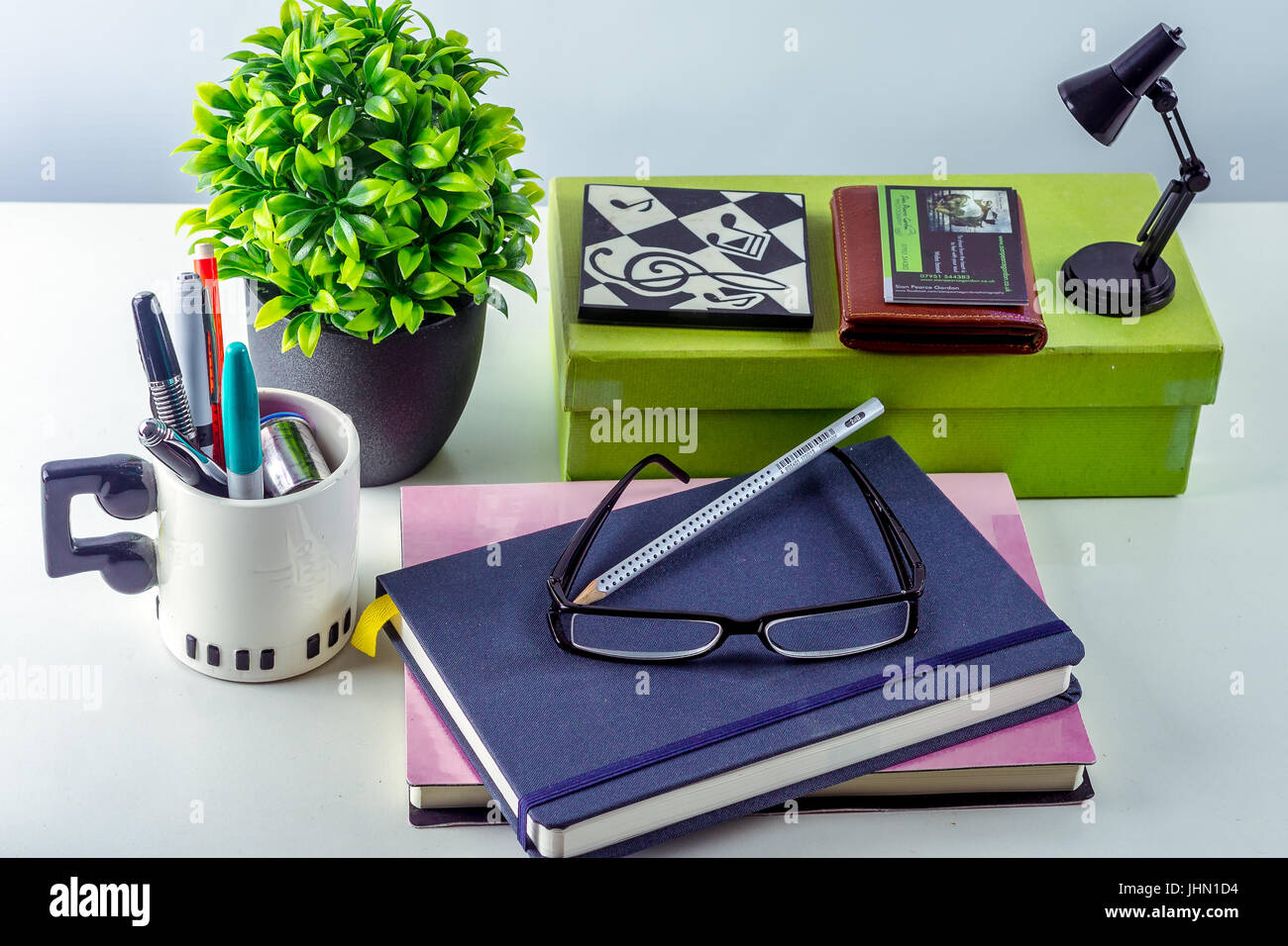 Modern White Office Desk With Accessories Including Plant, Reading Glasses,  Books, Business Cards, Pens, Mug U0026 Small Lamp