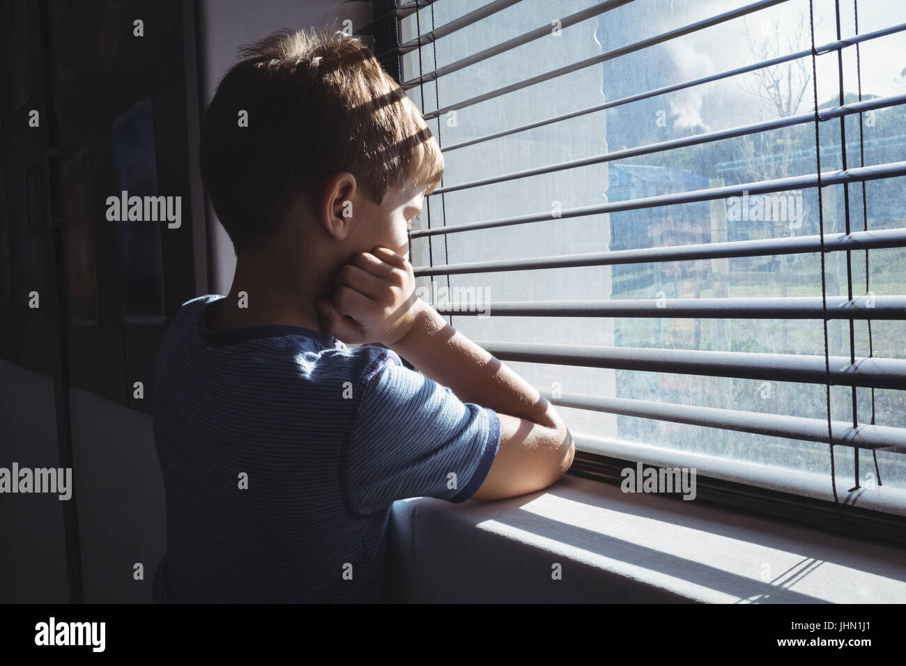 Side view of boy looking through window glass of school - Stock Image