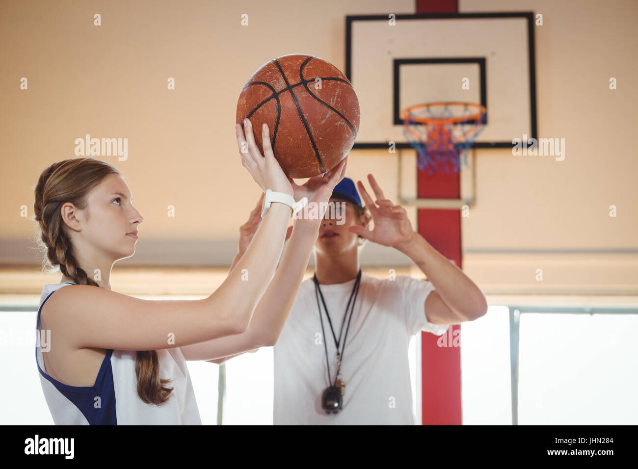 Coach advising female basketball player while practicing in court - Stock Image