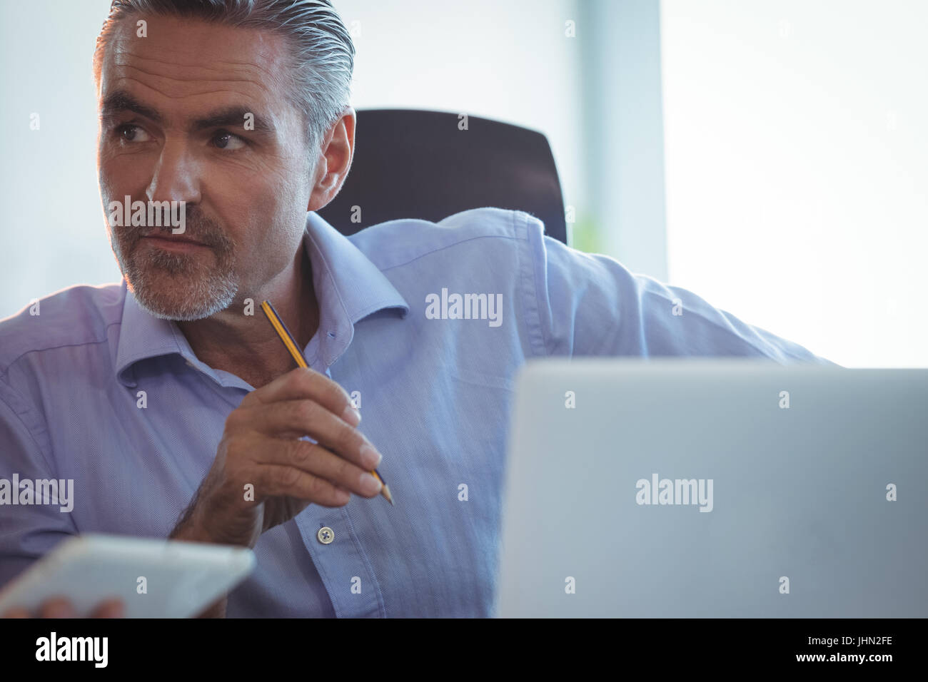 Concentrated businessman looking away in office - Stock Image