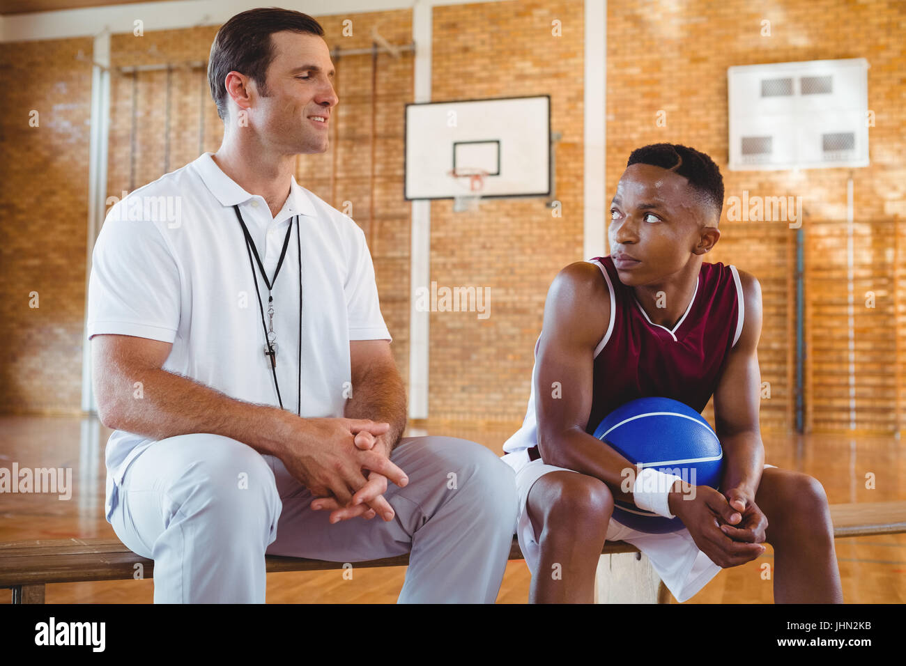 Smiling coach guiding basketball player while sitting on bench in court - Stock Image