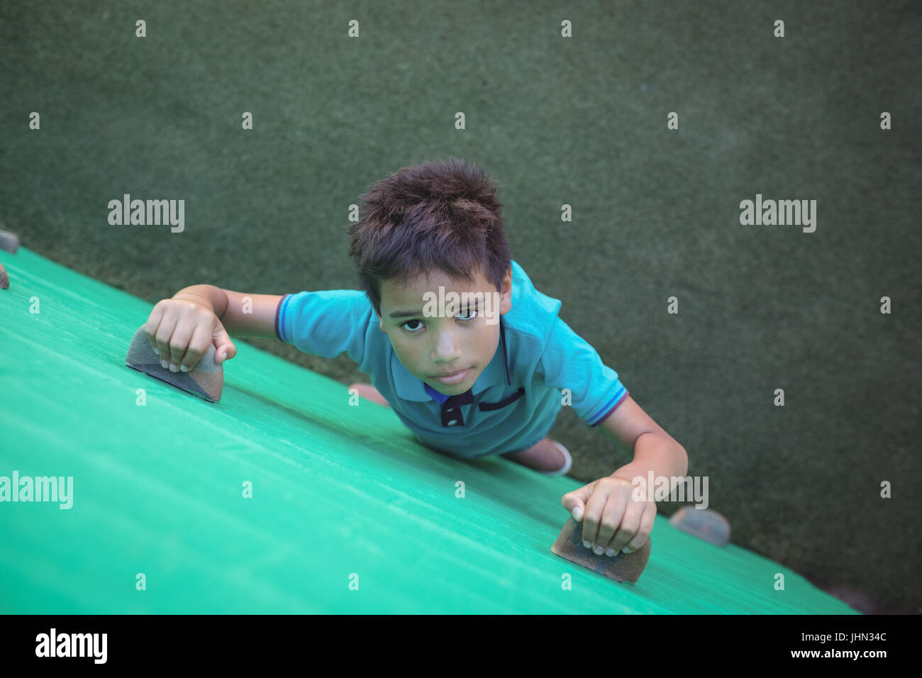High angle portrait of boy climbing green wall - Stock Image
