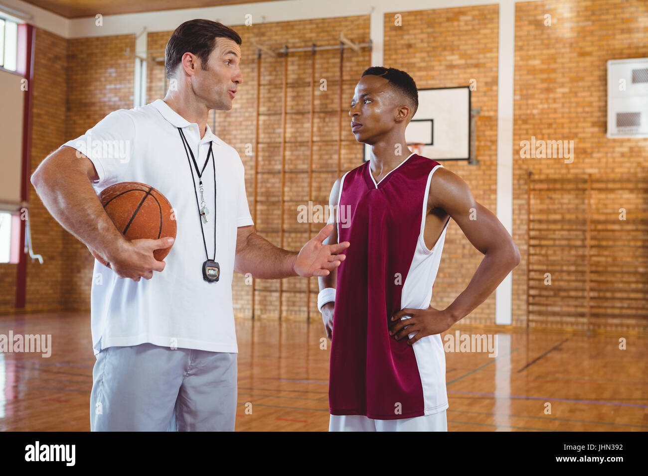 Coach guiding basketball player while standing in court Stock Photo