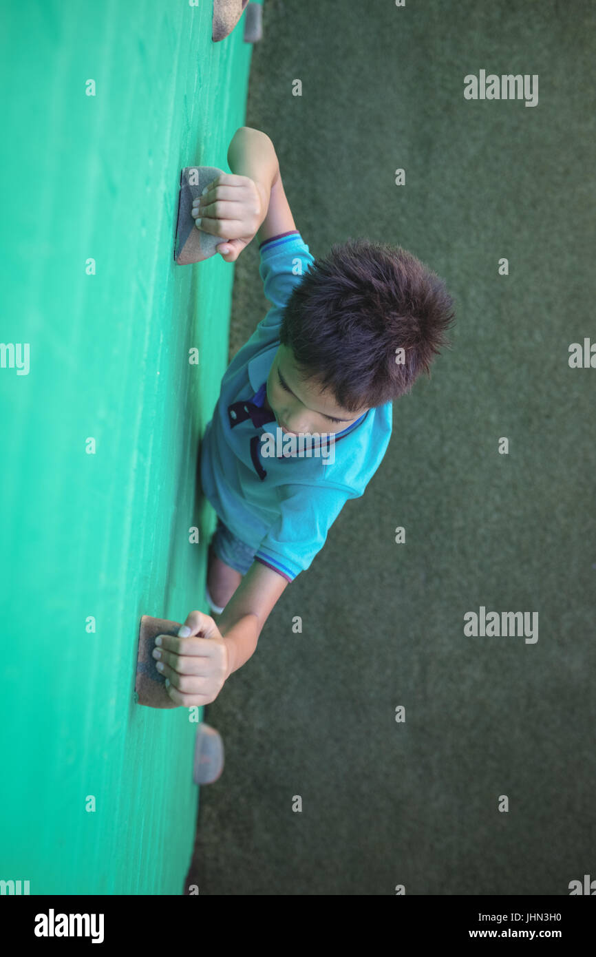 High angle view of boy gripping climbing holds on wall - Stock Image