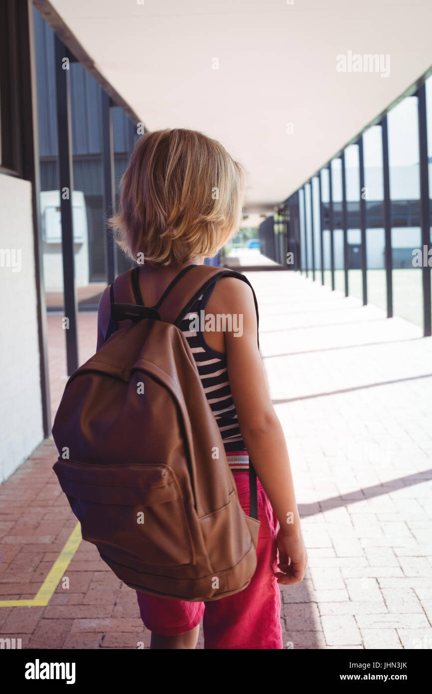 Rear view of schoolboy with backpack standing in corridor at school on sunny day Stock Photo