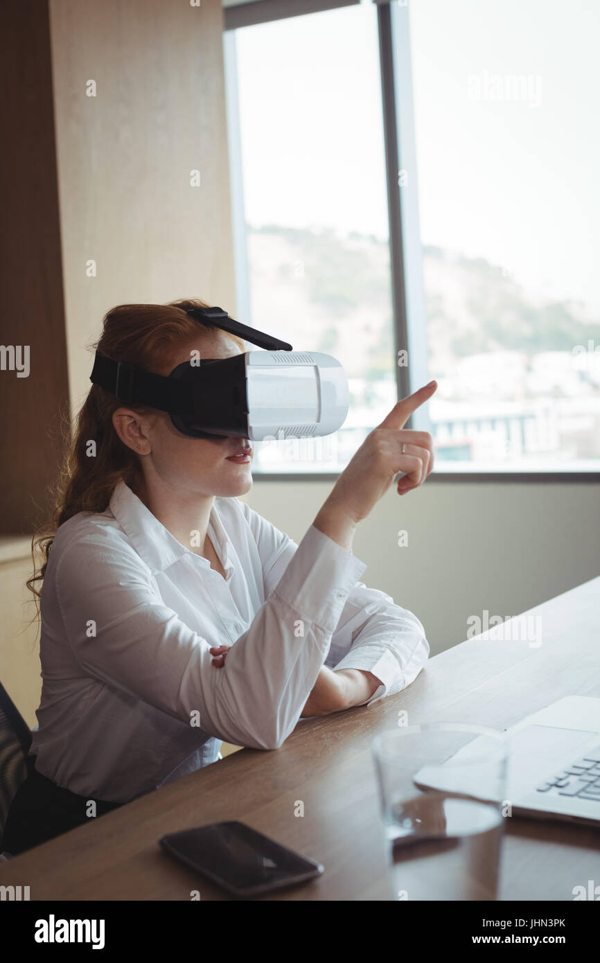Businesswoman anticipating while using virtual reality technology at desk in office - Stock Image
