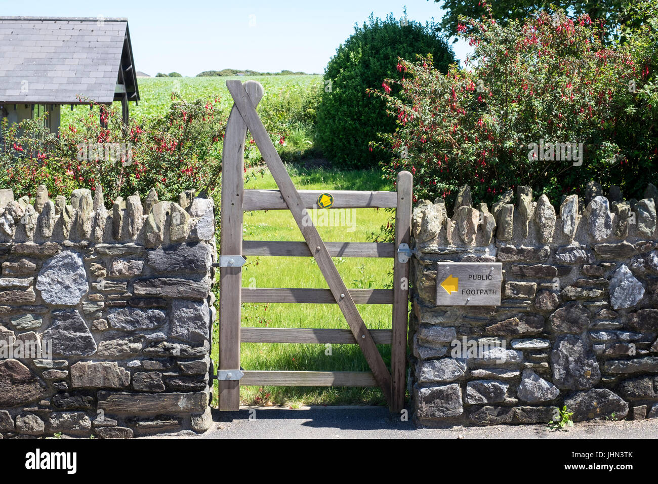 Gate in stone wall with Public Footpath right of way - Stock Image