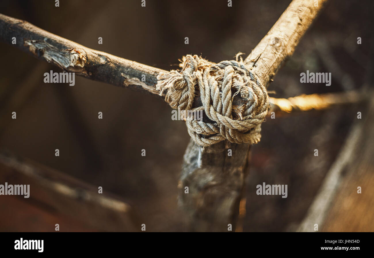 Knot of ropes on wooden brunches, part of small wooden fence. - Stock Image