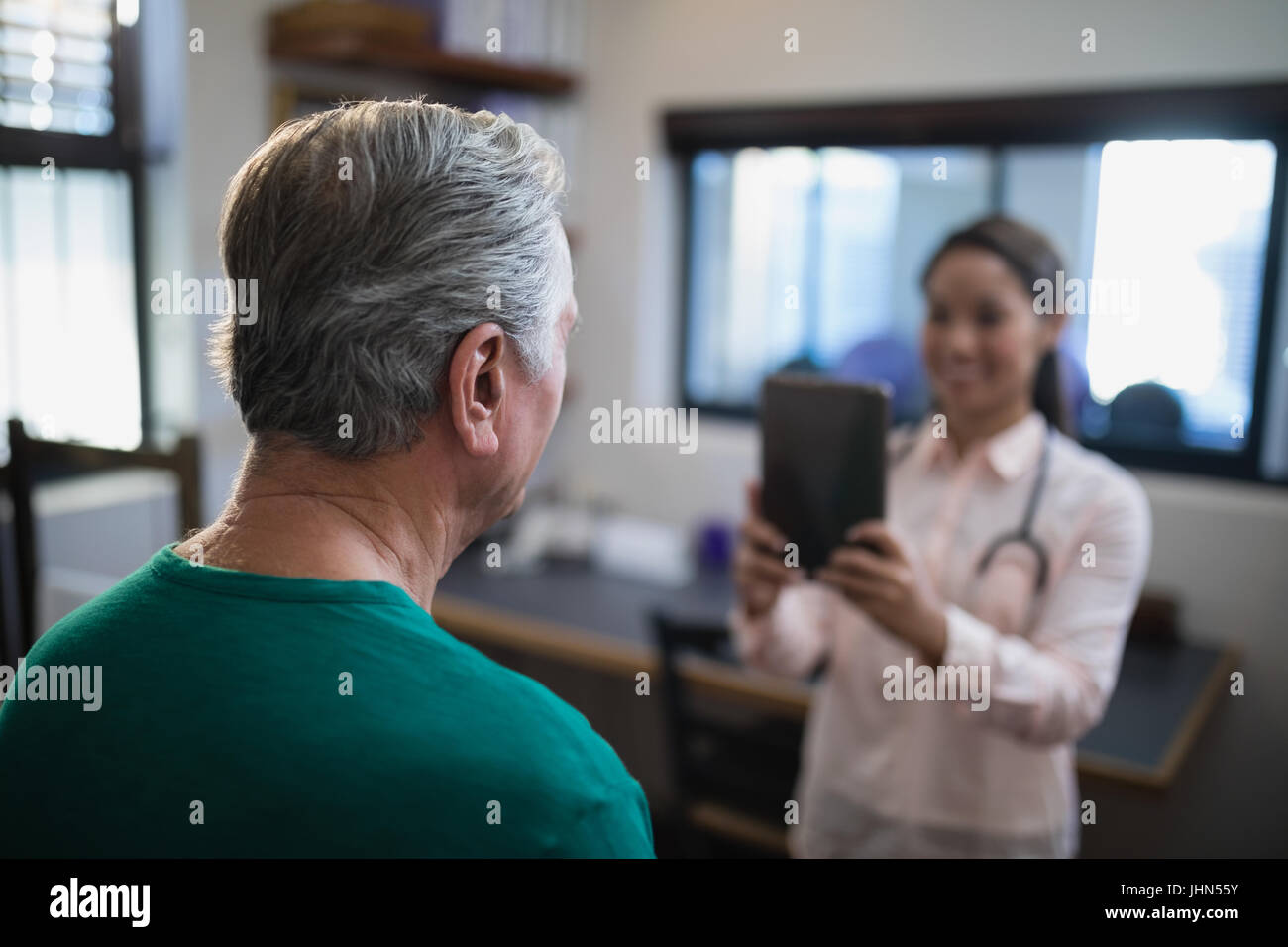Rear view of senior male patient being photographed by female therapist at hospital ward - Stock Image