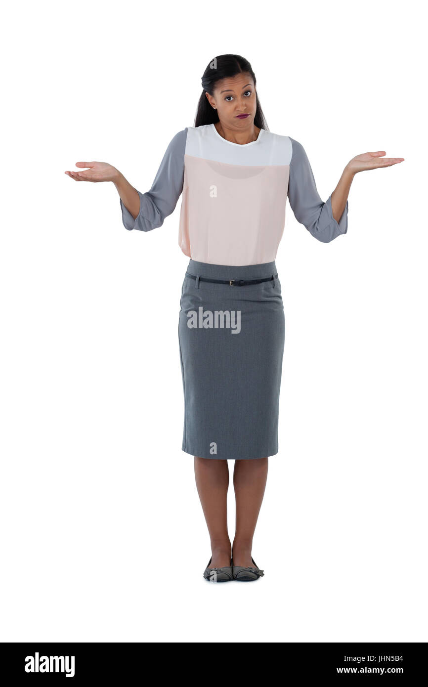Frowning businesswoman shrugging her shoulders against white background - Stock Image