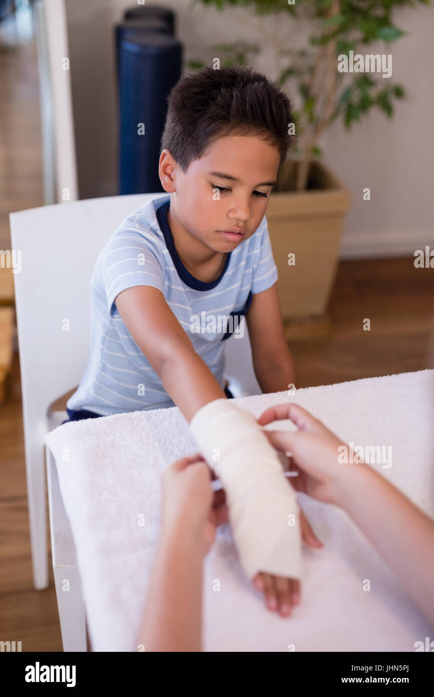 Boy looking at female therapist wrapping bandage on hand at hospital ward - Stock Image