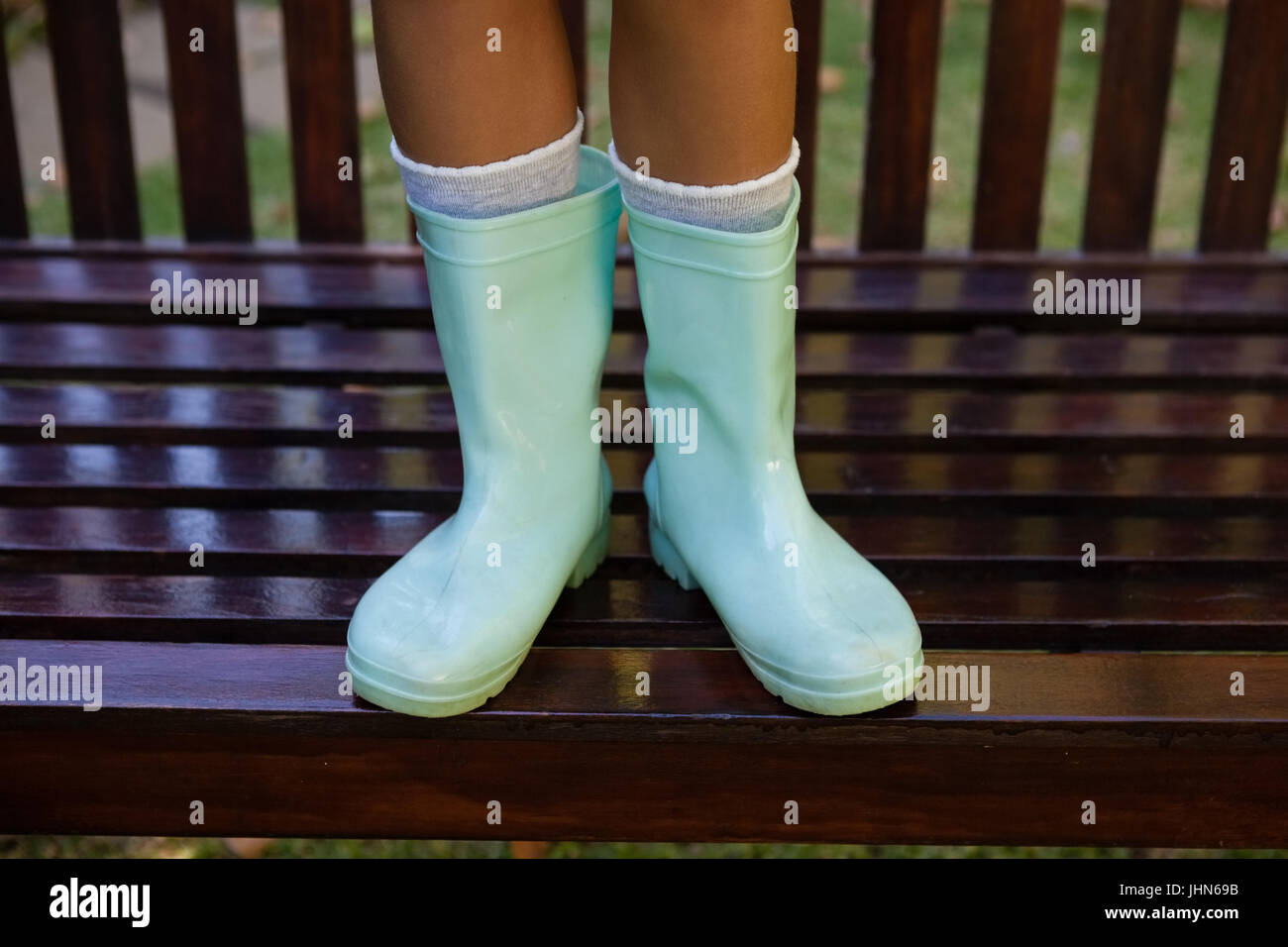 Low section of girl wearing green rubber boot standing on wooden bench at backyard - Stock Image