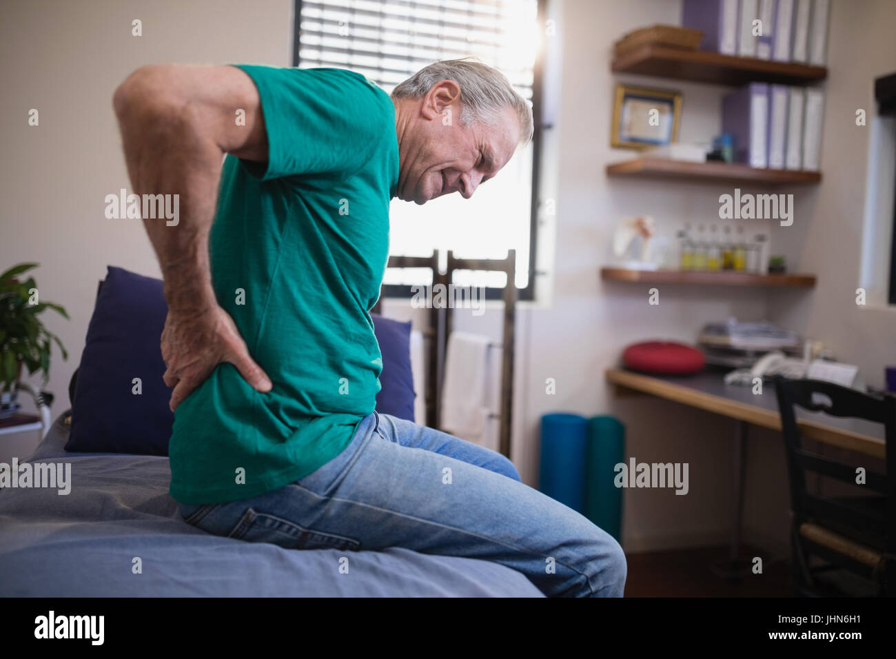 Side view of male patient grimacing from back ache while sitting on bed at hospital ward - Stock Image
