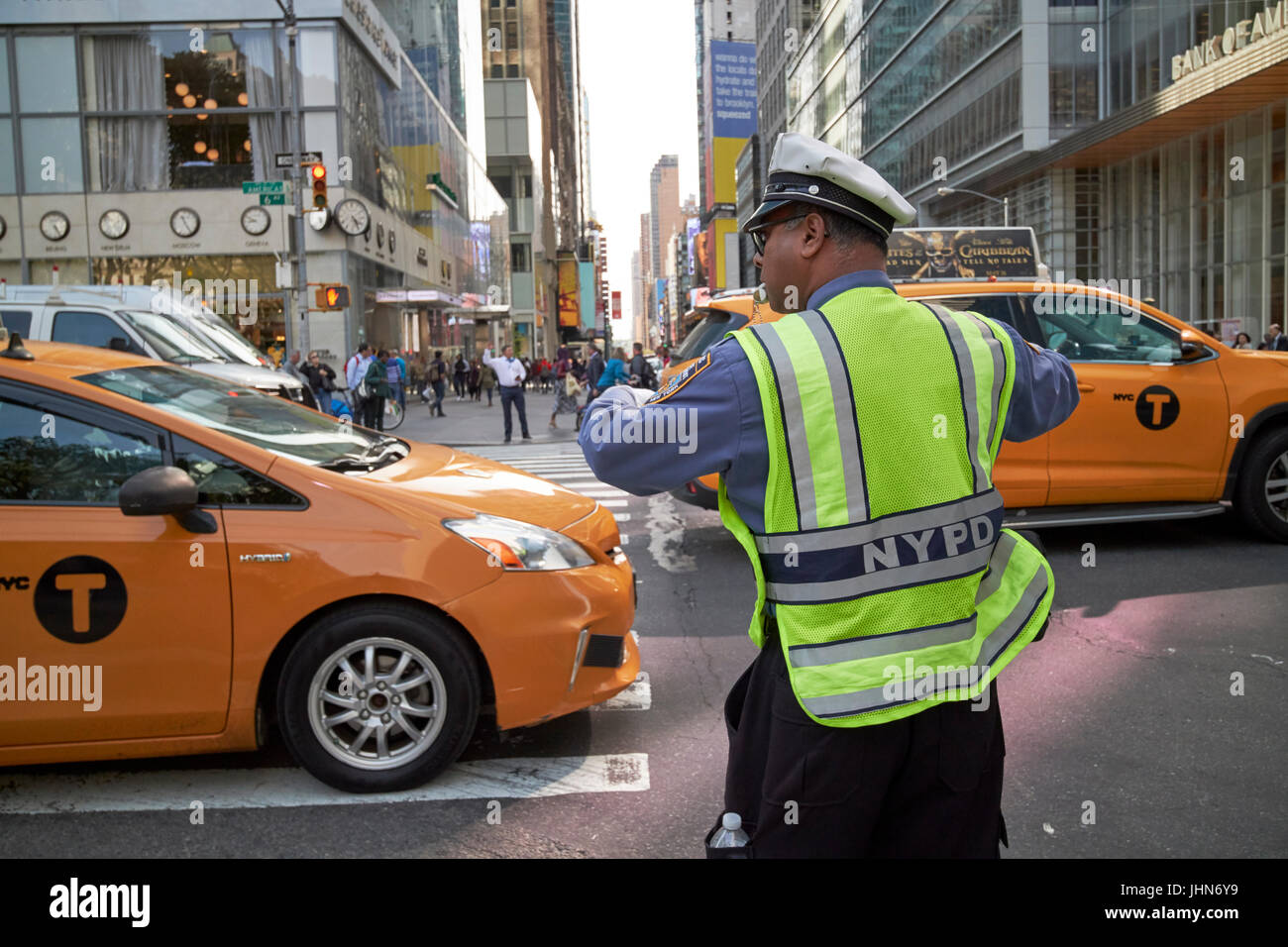 nypd traffic officer with whistle in mouth directing traffic on 6th ave New York City USA - Stock Image
