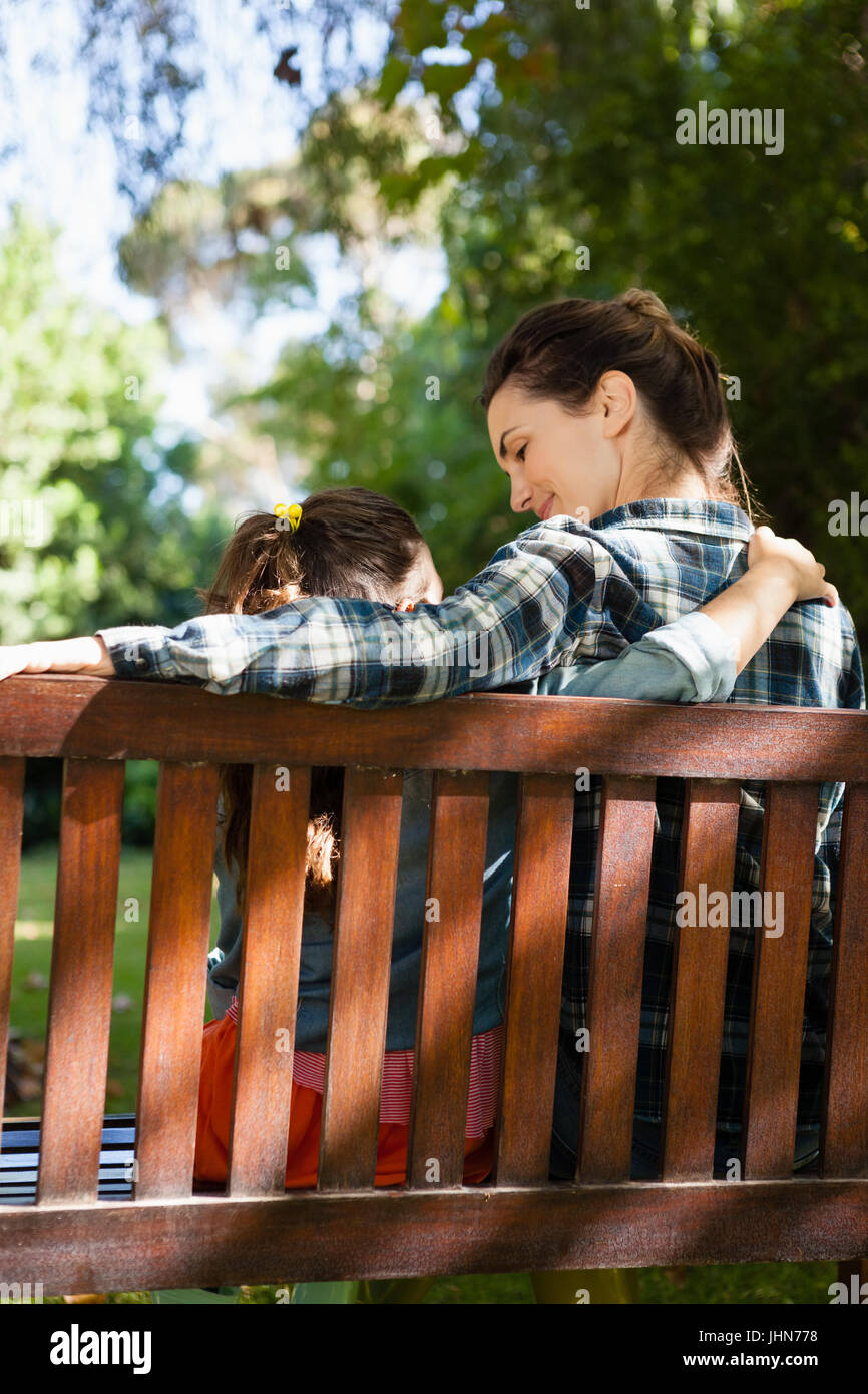 Rear view of mother and daughter sitting with arm around on wooden bench at backyard - Stock Image