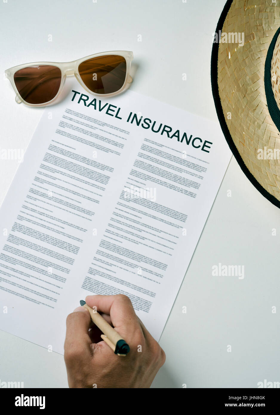 closeup of a young caucasian man signing a travel insurance contract on a white table, next to a pair of sunglasses - Stock Image