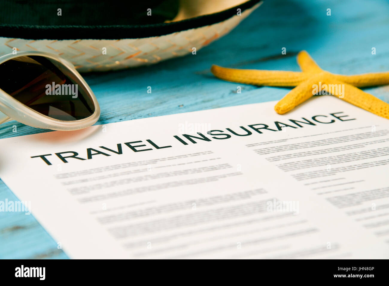 closeup of a travel insurance policy on a rustic blue wooden table, next to a pair of sunglasses, a straw hat and - Stock Image