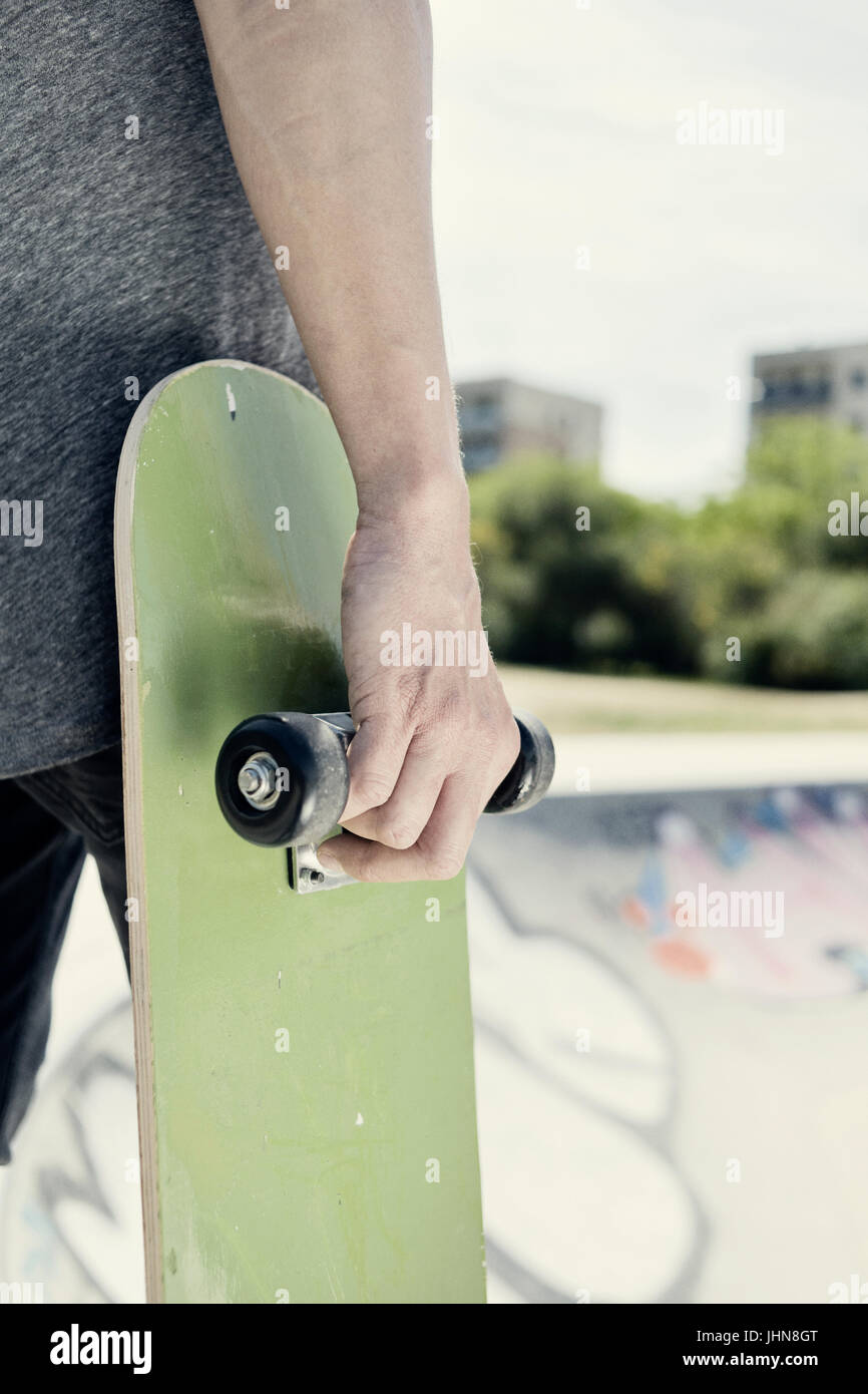 closeup of a young caucasian man with a skate board in his hand in an outdoors skate park - Stock Image