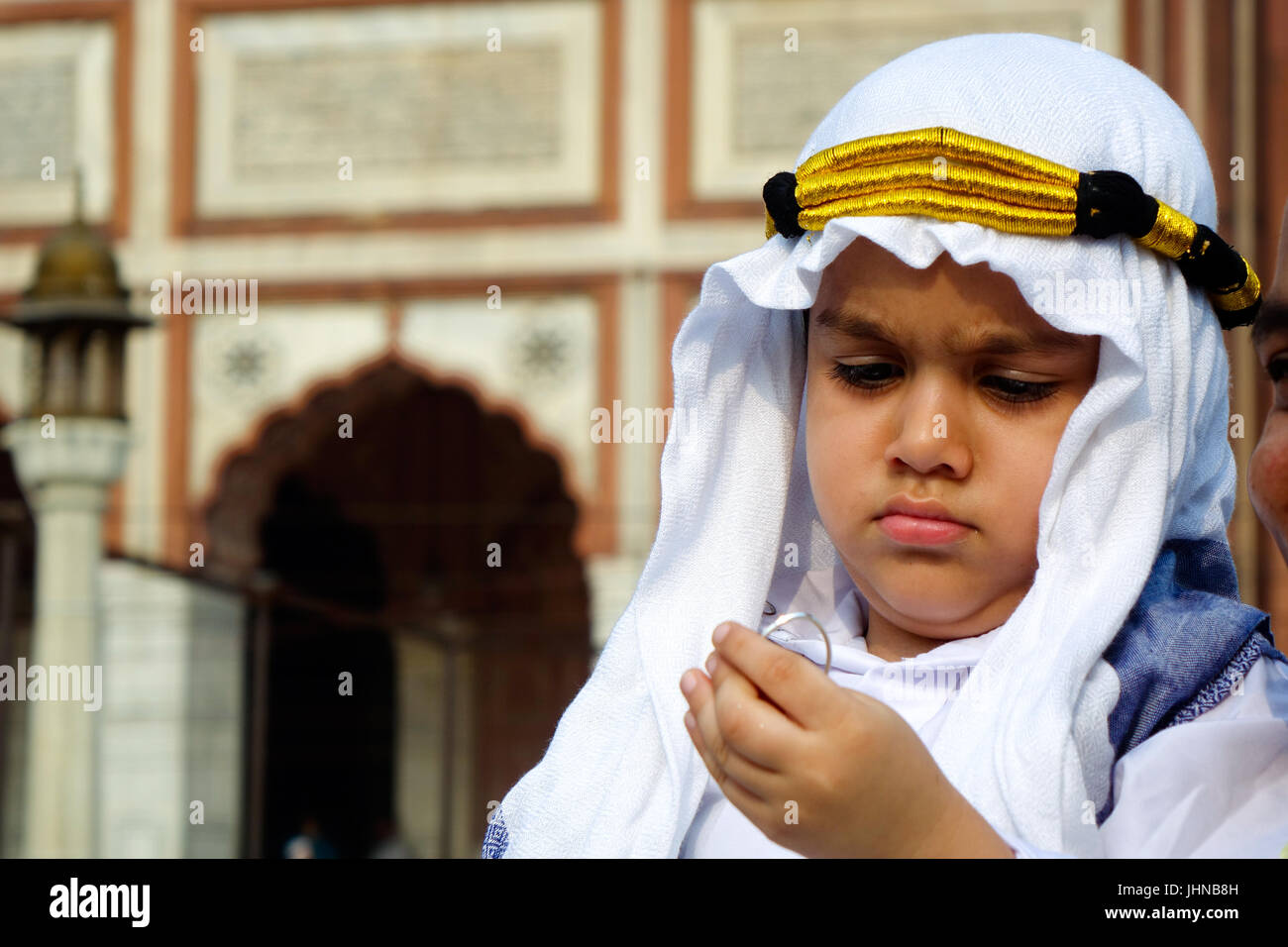 A adorable muslim child  dressed well in arabian sheik costume or outfit and enjoying on occasion of Eid Al Fitr - Stock Image