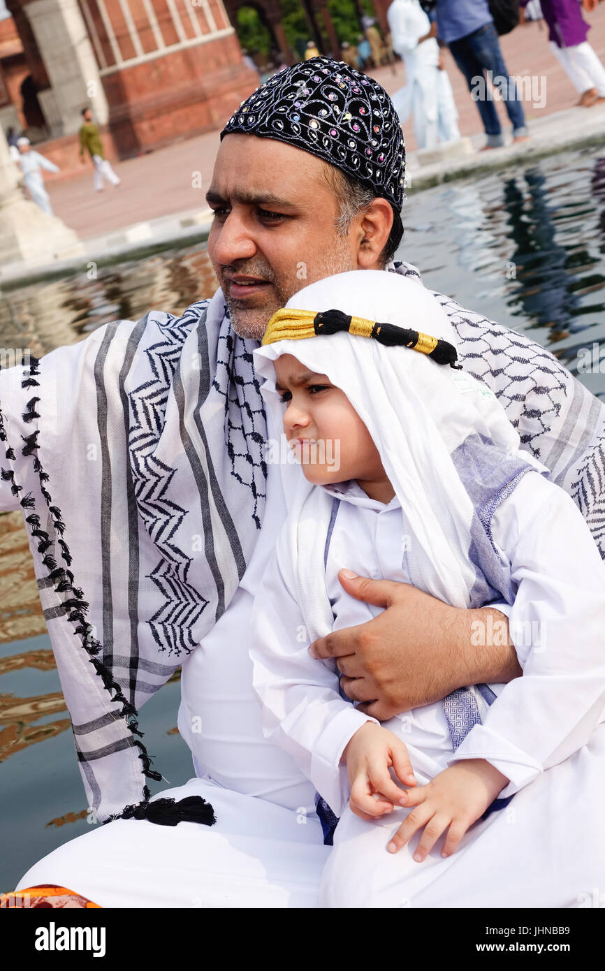 A adorable muslim child  dressed well arabian sheik costume or outfit and taking selfie with father celebrating - Stock Image