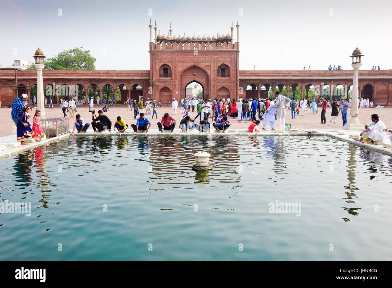 people at symmetrical architecture and holy islamic water pond i.e ablution pond inside jama masjid on occasion - Stock Image