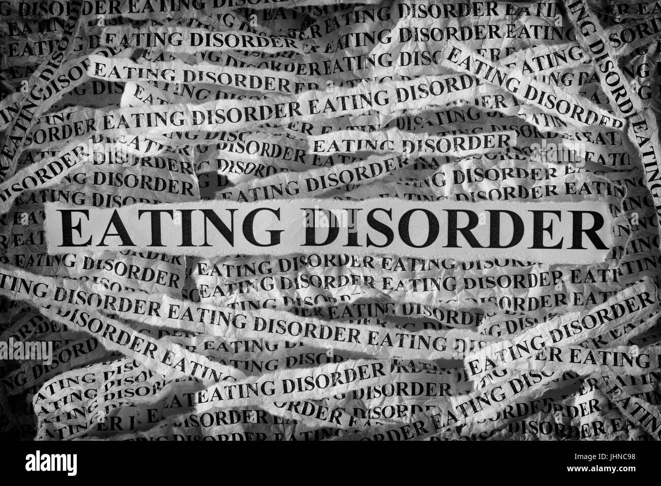 Eating Disorder. Torn pieces of paper with the words Eating Disorder. Concept Image. Black and White. Closeup. - Stock Image