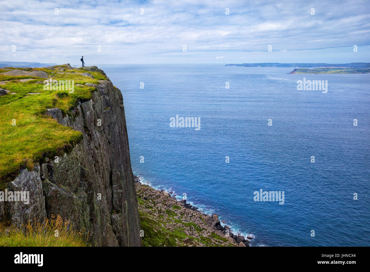 tourist with backpack standing on the cliff Fair Head, Northern Ireland, UK - Stock Image