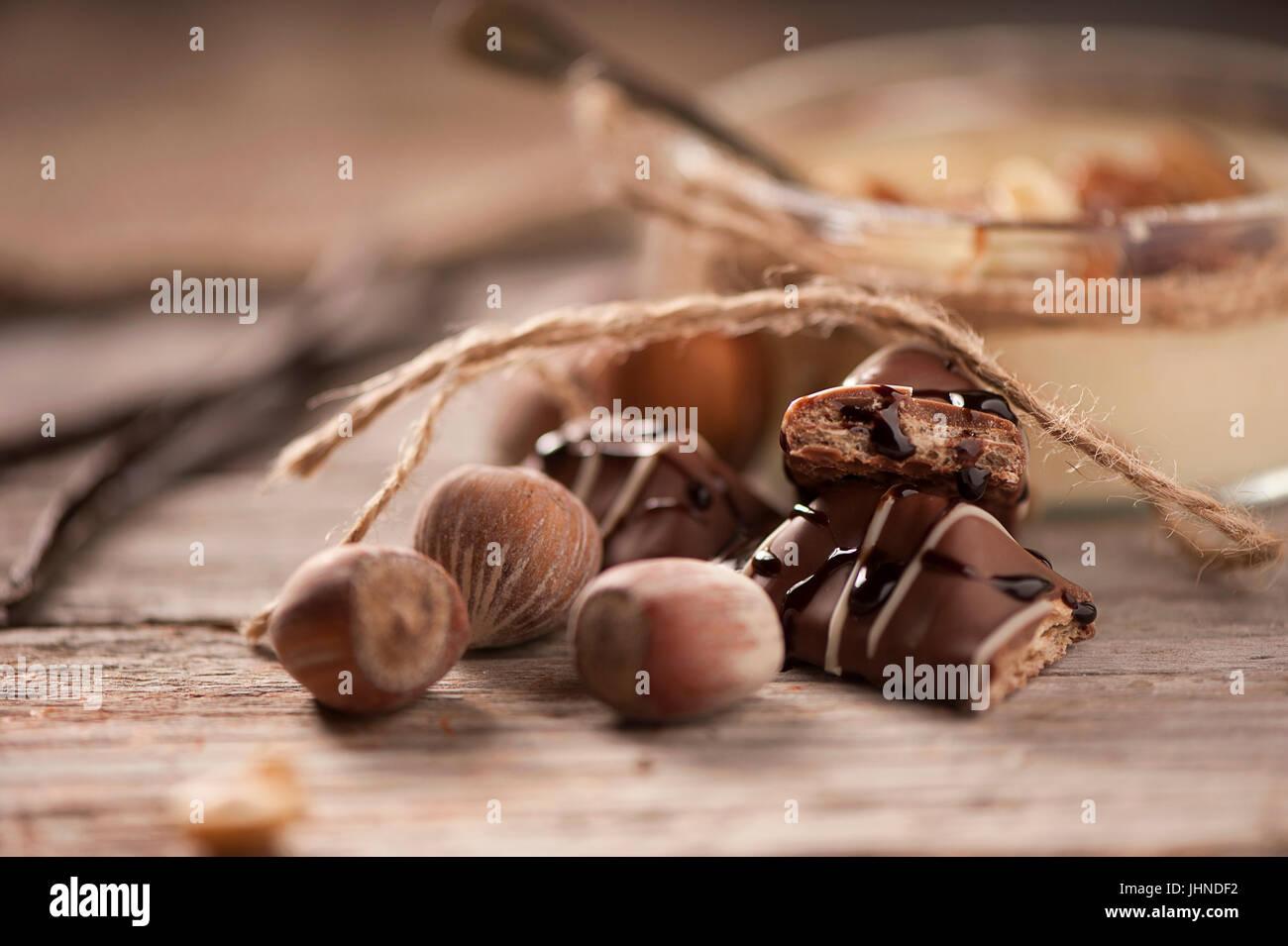 chocolate hazelnuts on wooden table background - Stock Image
