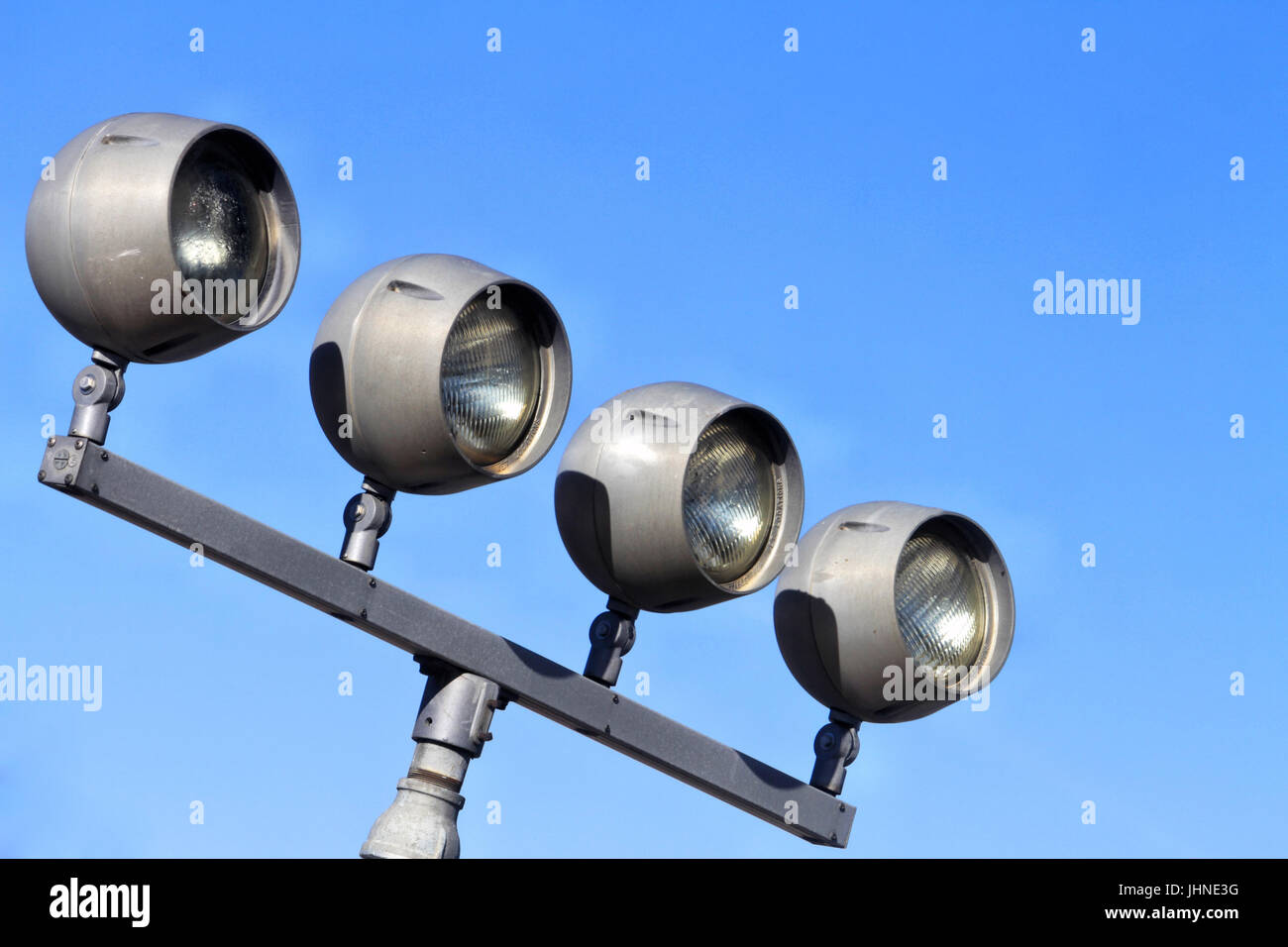A row of four outdoor unlit metal spotlights on a stand. - Stock Image