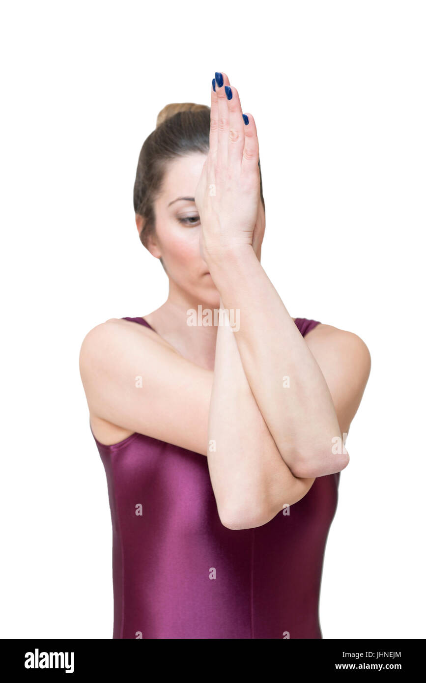 Woman practicing yoga in eagle pose isolated on the white background - Stock Image