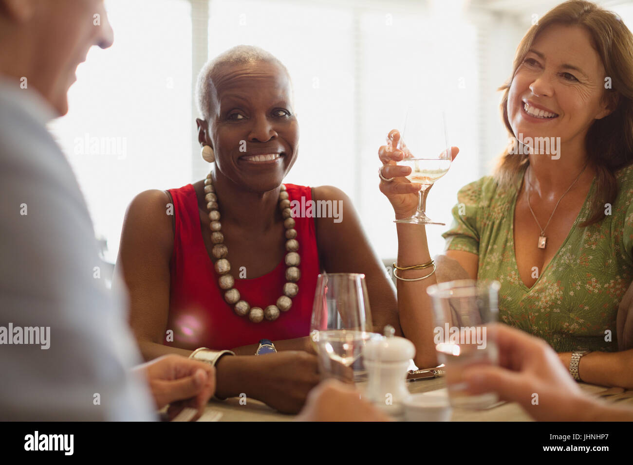 Mature friends dining at restaurant - Stock Image