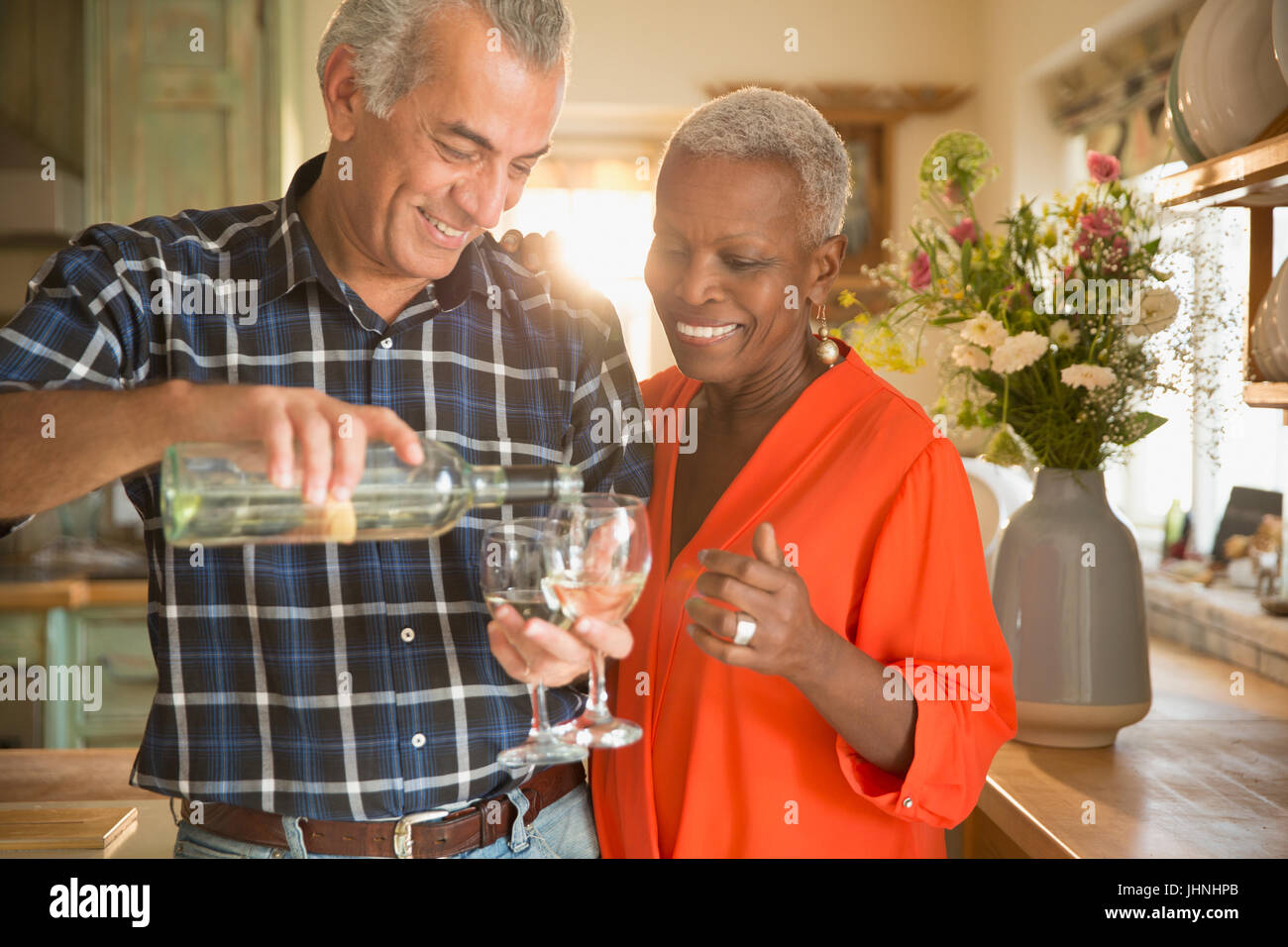 Smiling senior couple pouring white wine in kitchen - Stock Image